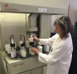 RPB technician, Bonnie Todd, arranging salmon samples on the gamma spectrometer for analysis.