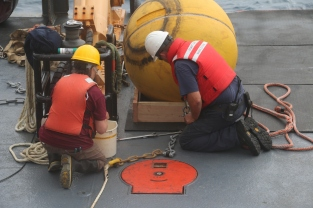 On deck working with an oceanographic mooring.