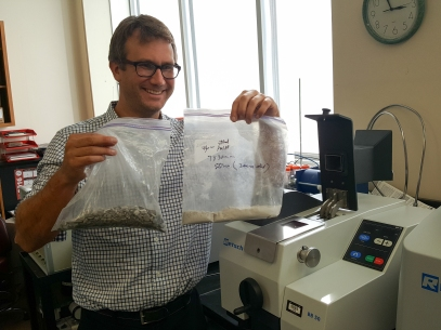 Dr. Mercier showing off the before and after of a rock sample that has gone through the crusher.